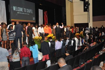 A worship leader leads prayer for young people on stage and in the audience in the Bethune-Cookman chapel